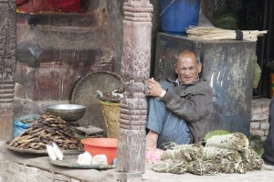 A relaxed shop keeper selling dried fish