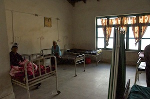 The men's ward with a patient. The beds are rusty!