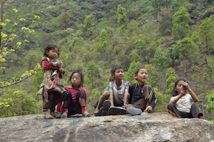 Young children watching the party from their rock